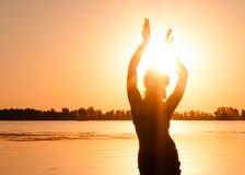 Kontur av den slanka kvinnan som dansar traditionell stam- magdans på stranden på soluppgång arkivbilder