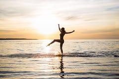 Kontur av den slanka sexiga flickan i bikini som går på stranden arkivfoto
