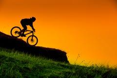 Kontur av den sluttande mountainbikeryttaren på solnedgången Arkivbild