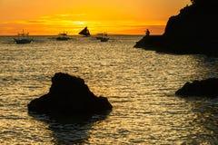 Kontur av den stora svarta stenen och segelbåten och tropisk ö på solnedgångFilippinerna Royaltyfri Bild