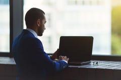 Kontur av den unga affärsmannen som sitter nära stort kontorsfönster fotografering för bildbyråer
