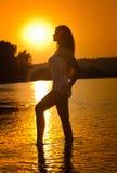 Kontur av den unga härliga kvinnan i floden över solnedgånghimmel Perfekt kroppkontur för kvinnlig på stranden i skymninglandskap arkivbilder