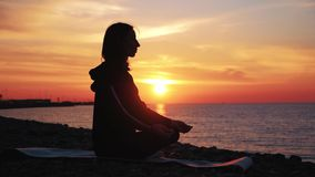 Kontur av den unga h?rliga sunda kvinnan som mediterar i lotusblommaposition vid havet p? solnedg?ngen ?vning f?r ung kvinna lager videofilmer