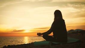 Kontur av den unga h?rliga sunda kvinnan som mediterar i lotusblommaposition vid havet p? solnedg?ngen ?vning f?r ung kvinna arkivfilmer
