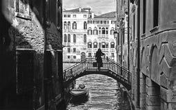 Kontur av den unga kvinnan på den lilla gamla bron mellan olden byggnader i smal vattenkanal och fasaden av historiskt b royaltyfria bilder