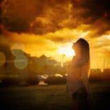 Kontur av den unga kvinnan på den stads- solnedgången Arkivbild