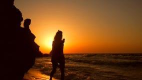 Kontur av den unga kvinnan som går med mobiltelefonen på stranden på den härliga guld- solnedgången Slowmotion HD 1920x1080 stock video