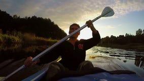 Kontur av den unga lyckliga mannen som paddlar kajaken på solnedgången, långsam-mo stock video