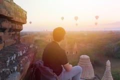 Kontur av den unga manliga fotvandraren som sitter och håller ögonen på ballongen för varm luft att resa destinationer i Bagan, M fotografering för bildbyråer