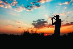 Kontur av den unga mannen som fotograferar solnedgången Royaltyfria Bilder