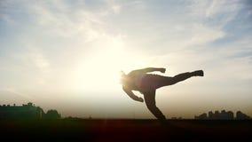Kontur av den unga mannen som gör utomhus akrobatiska beståndsdelar arkivfilmer