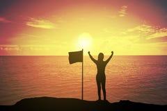 Kontur av den vinnande framgångkvinnan på solnedgången eller soluppgång som upp står och lyfter hennes hand nära flaggan i beröm fotografering för bildbyråer
