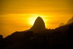 Kontur av det Dois Irmaos berget på bakgrunden av den guld- solen arkivfoton