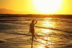 Kontur av det unga härliga flickaslutet upp nära havet på solnedgången Arkivfoto