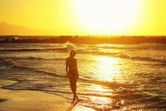 Kontur av det unga härliga flickaslutet upp nära havet på solnedgången Royaltyfri Bild