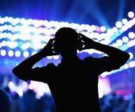 Kontur av discjockeyn som bär hörlurar och utför på en nattklubb Arkivfoto