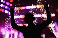 Kontur av discjockeyn som bär hörlurar och utför på en nattklubb arkivbilder