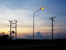 Kontur av elektriska poler och kablar över soluppgånghimmelbakgrund Arkivbild