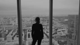 Kontur av en affärsman mot fönstret av en skyskrapa lager videofilmer