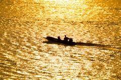 Kontur av en båtuthyrare i floden på guld- solsken Royaltyfria Bilder