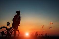 Kontur av en cyklist och en cykel på himmelbakgrund Royaltyfri Fotografi