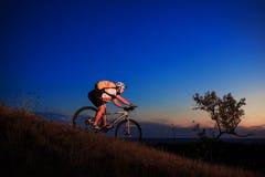 Kontur av en cyklist och en cykel på solnedgångbakgrund Royaltyfria Foton