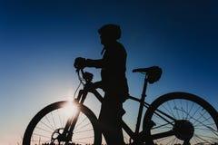Kontur av en cyklist som rider cykeln ner Rocky Hill p? solnedg?ngen Extremt sportbegrepp royaltyfri foto