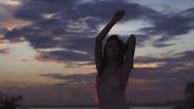 Kontur av en dansflicka på en bakgrundssolnedgång härlig flickadans och ha roligt utomhus arkivfilmer