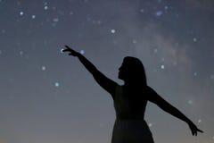 Kontur av en danskvinna som pekar i natthimmel Kvinnakontur under stjärnklar natt, Defocused Vintergatangalax Fotografering för Bildbyråer