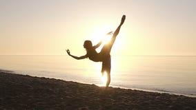 Kontur av en elegant ballerina i en ballerinakjol i strålarna av morgonsolen Göra övningar som öva seashore långsamt stock video