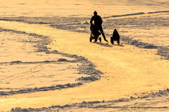 Kontur av en familj som åker skridskor på is under solnedgång i Holland Royaltyfri Foto