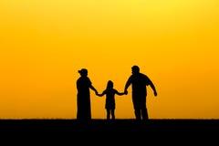 Kontur av en familj som går i solnedgång Royaltyfria Bilder