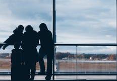 Kontur av en familjgrupp som ser panorama och v?ntar i flygplatsen royaltyfri bild