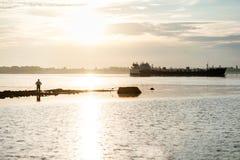 Kontur av en fiskare och en pråm Arkivbilder
