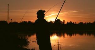 Kontur av en fiskare på en solnedgångbakgrund arkivfilmer