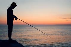 Kontur av en fiskare p? solnedg?ngen royaltyfri fotografi