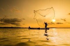 Kontur av en fiskare som kastar hans netto med solnedgång Arkivbilder