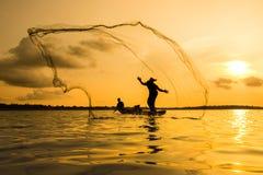 Kontur av en fiskare som kastar hans netto med solnedgång Royaltyfri Foto