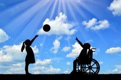 Kontur av en flicka för rörelsehindrat barn i en rullstol och den sunda flickan som spelar i en boll utomhus arkivbild
