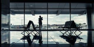 Kontur av en flicka i en flygplatsterminal Royaltyfria Bilder