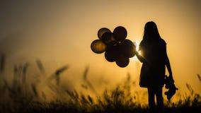 Kontur av en flicka med ballonger och en nallebjörn Det är värde solnedgången Avsked till barndombegreppet royaltyfri foto