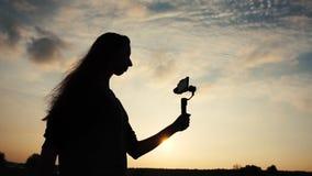 Kontur av en flicka med smartphonen på stabilisatorn i hennes händer, ultrarapid arkivfilmer