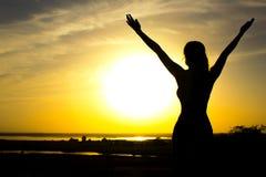 Kontur av en flicka som lyfter händer till himlen efter gymnastik, en kvinna som tycker om solnedgången royaltyfri bild