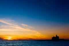 Kontur av en fyr på solnedgången Arkivbild