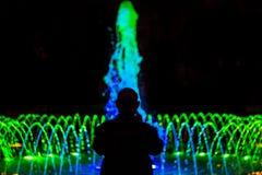 Kontur av en gamal man framme av springbrunnen med kulör belysning royaltyfria bilder