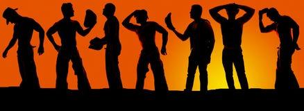 Kontur av en grupp av cowboyer i solnedgången Arkivbild