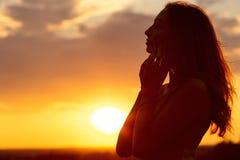 Kontur av en härlig romantisk flicka på solnedgången, framsidaprofil av den unga kvinnan med långt hår i varmt väder fotografering för bildbyråer