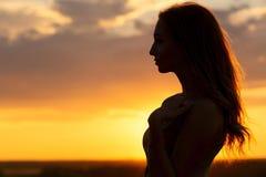 Kontur av en härlig romantisk flicka på solnedgången, framsidaprofil av den unga kvinnan med långt hår i varmt väder arkivfoto