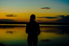 Kontur av en hållande ögonen på solnedgång för ung kvinna på sjön royaltyfria bilder