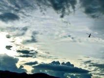 Kontur av en helikopter mot en grå himmel med moln royaltyfri foto